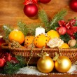 Christmas composition in basket with oranges and fir tree, on wooden background - Foto Stock