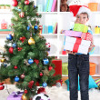Little boy in Santa hat stands near Christmas tree with gifts - Zdjęcie stockowe