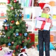 Little boy in Santa hat stands near Christmas tree with gifts - Foto Stock