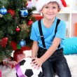 Little boy in Santa hat sits near Christmas tree with football ball - ストック写真