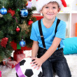 Little boy in Santa hat sits near Christmas tree with football ball - Zdjęcie stockowe