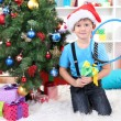 Little boy in Santa hat sits near Christmas tree with badminton rackets - Zdjęcie stockowe