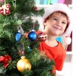 Little boy in Santa hat peeks out from behind Christmas tree - Zdjęcie stockowe