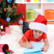 Little boy in Santa hat writes letter to Santa Claus - Foto Stock