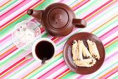 Widok z góry o filiżankę herbaty i czajnik na kolorowe obrusy — Zdjęcie stockowe