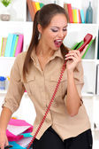 Angry businesswoman with phone at office — Stock Photo