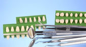 Set of dental tools with denture on blue background — 图库照片