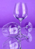 Two empty wine glasses on color background — Stock Photo
