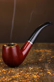 Smoking pipe and tobacco on wooden table on brown background — Stock Photo