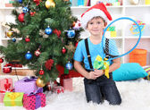 Little boy in Santa hat sits near Christmas tree with badminton rackets — Stock Photo