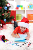 Little boy in Santa hat writes letter to Santa Claus — Foto de Stock