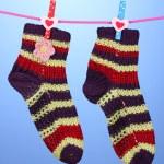 par de tricotar meias listradas pendurado para secar sobre fundo azul — Foto Stock #16618947