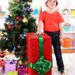 Child in Santa hat near Christmas tree with big gift — Stock Photo #16681863