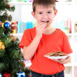 Little boy near Christmas tree eats cookies — Stock Photo #16682001