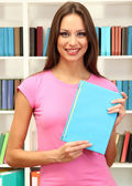 Young attractive female student with book in library — Stock Photo