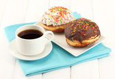 Tasty donuts on color plate on light wooden background — 图库照片