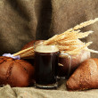 Tankard of kvass and rye breads with ears, on burlap background — Stock Photo #16767391