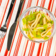 Salad of squid rings, lemon and lettuce in a glass bowl on striped tablecloth close-up — Stock Photo #16767557
