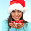 Beautiful young woman holding snow with christmas balls, on blue background — Stock Photo