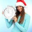 Beautiful young woman with clock, on blue background — Stock Photo #16769975