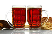 Tankards of kvass and rye breads with ears, isolated on white — Stock Photo