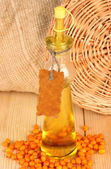 Decanter with sea buckthorn oil on wooden background close-up — Stock Photo