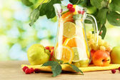 Jar with citrus fruits and raspberries, on green background — Stock Photo