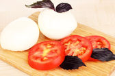 Tasty mozzarella with tomatoes on chopping board on mat — Stock Photo