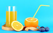 Ripe oranges and juice as symbol of diet on blue background — Stock Photo