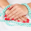 Female hands holding beads on color background — Stock Photo