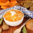 Useful pumpkin porridge in white plate on wooden table close-up - Stock Photo
