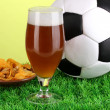 Glass of beer with soccer ball on grass on green background — Stock Photo #16772725