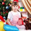 Little girl sits near a Christmas tree with gift in hand in festively decorated room — Stock Photo