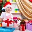 A little girl opens a gift in festively decorated room — Stock Photo #16774929