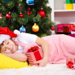 The little girl fell asleep with gift in their hands in festively decorated room — Stock Photo #16774949