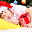 The little girl fell asleep with gift in their hands in festively decorated room — Stock Photo #16774971