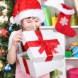 A little girl opens a gift in festively decorated room — Stock Photo #16774991