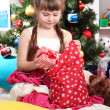 Stock Photo: Little girl gets gifts from bag of SantClaus in festively decorated room