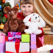 Stock Photo: Beautiful little girl in red dress surrounded by gifts and toys in festively decorated room