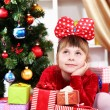 Stock Photo: Dreaming little girl in red dress surrounded by gifts in festively decorated room