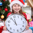 Beautiful little girl with clock in anticipation of New Year in festively decorated room — Stok Fotoğraf #16775095