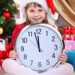 Beautiful little girl with clock in anticipation of New Year in festively decorated room — Stock Photo #16775115