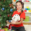 Little girl holding toy near christmas tree — Stock Photo #16775885