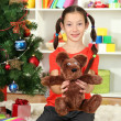 Stock Photo: Little girl holding toy near christmas tree