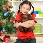 Little girl holding toy near christmas tree — Stock Photo #16775911