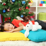 Little girl sleeping near christmas tree — Stock Photo #16775913