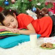 Little girl sleeping near christmas tree — Stock Photo