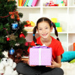 Little girl holding gift box near christmas tree — Stock Photo #16775949
