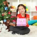 Little girl holding gift box near christmas tree — Stock Photo #16775965