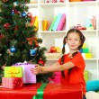 Little girl with large gift box near christmas tree — Stock Photo #16775971